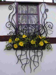 Вьющееся кованое изделие для цветов на окна